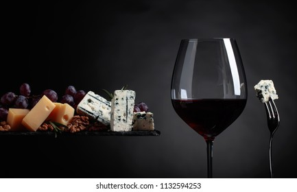 Glass of red wine with various cheeses , grapes and walnuts on a black background.Copy space .