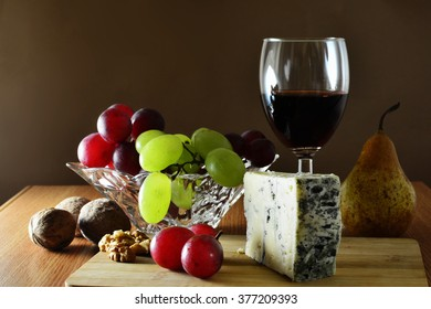 Glass of red wine with a wedge of French blue cheese, grapes and fruits on wooden board.