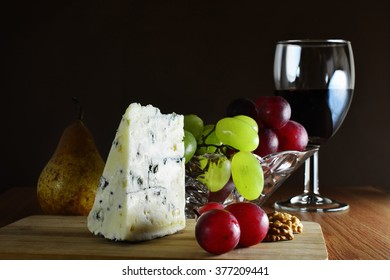 Glass of red wine with a wedge of French blue cheese with grapes  on wooden board.