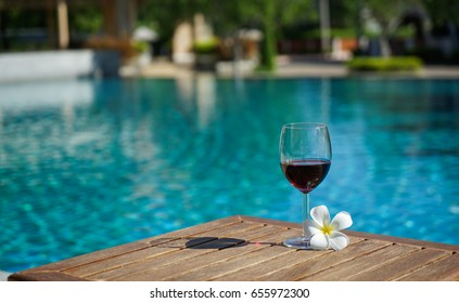 Glass of red wine and a white tropical flower on sunbed near a swimming pool in a late morning of summer, clubhouse in background.