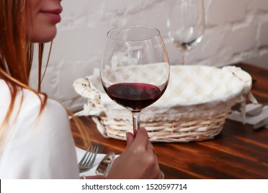 A glass of red wine in a woman's hand. Unrecognizable photo, photo without a face. Close-up in the interior of a restaurant or cafe. Out of focus. Macro photo.