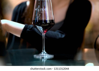 Glass of red wine and a women hand in luxury restaurant.