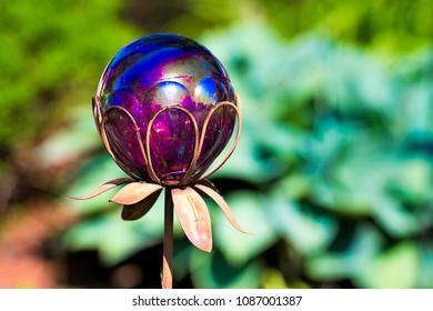 Glass reflected ball garden ornament in garden.