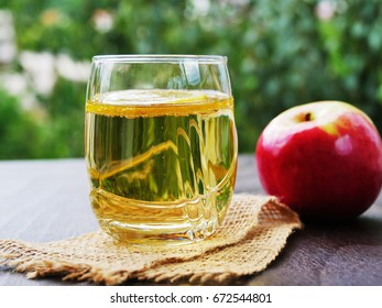 Glass of refreshing apple cider on wooden table