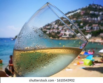 A Glass of refreshing cold white wine close up on beach restaurant.Ice beverage with chardonnay or sauvignon with drops of water condensate on blurred background of coastline of resort town in Spain.