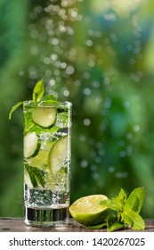 in a glass a refreshing summer drink with cucumber and lime, large gas bubbles, in the background water drops are out of focus, concept, close-up