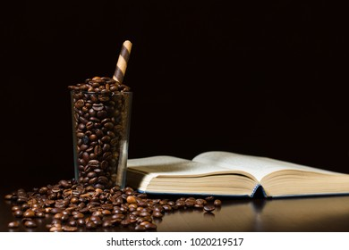 Glass of roasted coffee beans on wooden table with open book and black background - copy space.