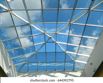 Glass roof with blue sky and clouds