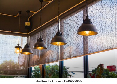 Glass room and curtain, Louvers , shade, blinds, shutters window decoration concept with vintage lamp hanging from the black ceiling.
