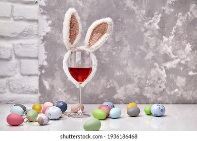 Glass of rose or red wine with bunny ears and Easter decorations, colorful eggs on white table, on bright background. Copy space for text.