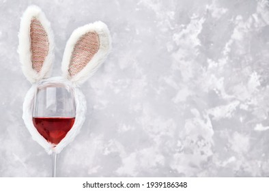 Glass of rose or red wine with bunny ears on bright background. Easter decorations concept. Copy space for text.
