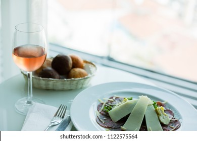 Glass of rose wine and beed carpaccio (selective focus)