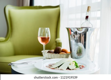 Glass of rose wine and cheese board in a hotel room (selective focus)