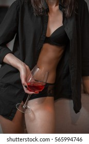 glass of rose wine in drunk woman's hand