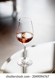 Glass of rose wine in wine library or bar. Alcohol beverage on table.