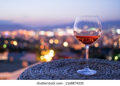 Glass of Rose Wine in a majestic sunset background with beautiful city lights.