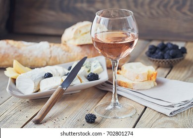 A glass of rose wine served with cheese plate, blackberries and baguette. Assortment of cheese with berries on wooden background.