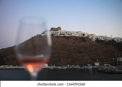 A glass of rose wine with the view of the fortress in the island of Astypalaia in Greece.