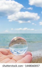 The glass round ball on the hand reflects the beach in the summer
