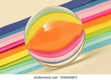 A Glass Round Lensball and Paper Rainbow reflexion
