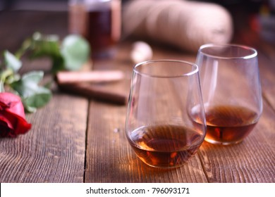 Glass of rum on a rustic wooden table with cigars and bottle.