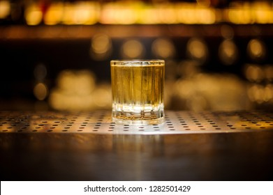 Glass of a Rusty Nail cocktail on the wooden steel bar counter on the light blurred background