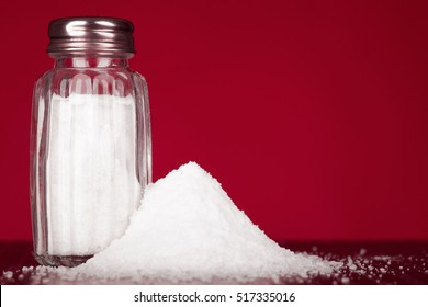 glass salt shaker on black table and red background