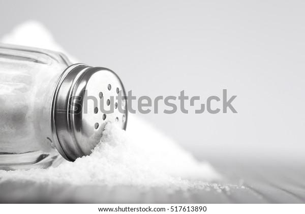 Glassalzschüttler auf grauem Tisch und weißem Hintergrund für Text