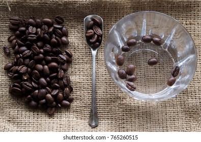 Glass of sambuca, Italian liquor, on a jute canvas with coffee beans