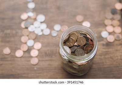 glass savings jar filled with coins isolated on wooden table.