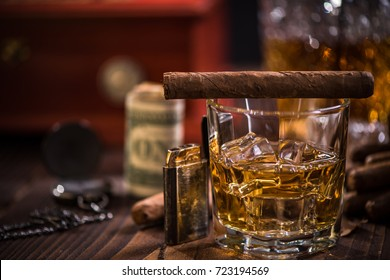 Glass of Scotch or Cognac over ice cubes and Cigar on wooden table