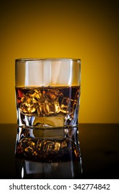 Glass of scotch whiskey and ice with reflection on black background