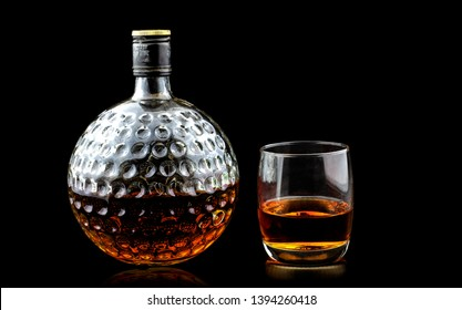 Glass of scotch whiskey premium and old decanter isolated on a black background