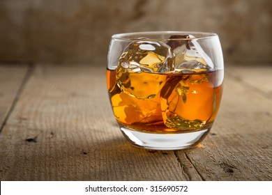Glass of scotch whisky brandy with ice on wooden bar table rustic barrel surface