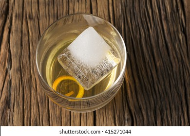 Glass of Scotch whisky on an old rustic wooden background. Modern styling with one large ice cube and orange peel as a garnish.