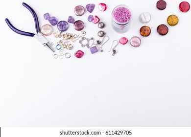 Glass seed and bugle beads, amethyst and turmaline stones, silver toggle, metal beads, shell rose beads, earings, metal rings and pliers on white background. Top view.