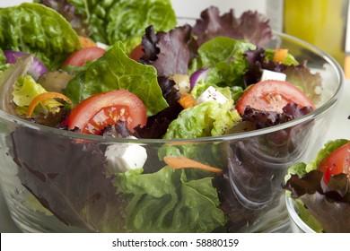 Glass serving bowl of fresh green salad.