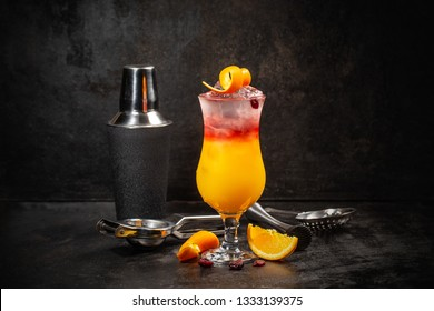 Glass of Sex on the Beach cocktail and shaker against dark background