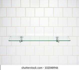 Glass shelf on white wall.