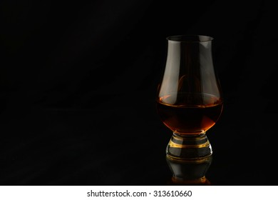 Glass with single malt whisky isloated over black background