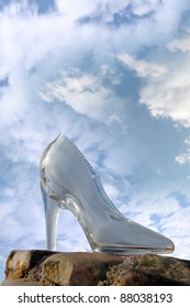 a glass slipper on a stone surface with a cloudy blue sky background