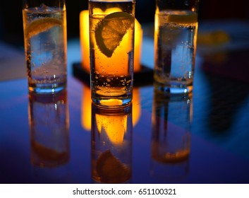 A glass of soda with bubbles of gas in the light of a candle on a lumen with a slice of lemon in it with a dark tonality