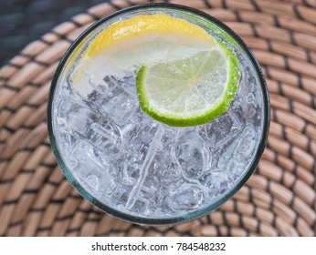 Glass of soda water with ice-cubes, a slice of lime and a slice of lemon. The glass is seen directly from above, standing on a round placemat. Only the glass and its content is in focus.