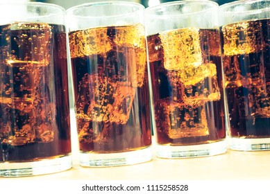 Glass of soda waters or cola is a sweetened and carbonated drink, which including of caffeine. Side view of refreshing cola soda with bubbles and ice on top.