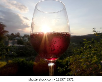 """A glass of soft red wine (""""vino frizzante rosso amabile"""") at sunset with green background landscape"""