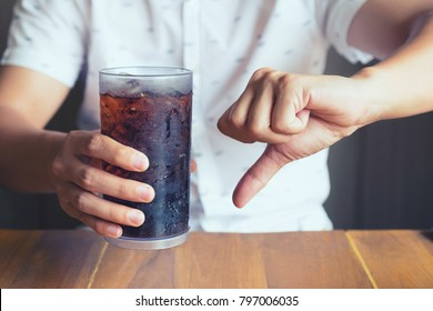Glass of softdrink splashing with ice on hand wooden table background, not good bad for health  finger symbol