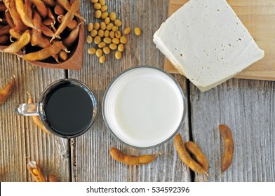 Glass of soy milk, soy sauce and soy tofu on a wooden table, top view. Soy food