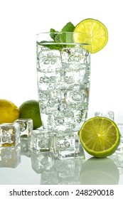 Glass of sparkling  water with ice cubes garnished with a slice of lime and mint on white background