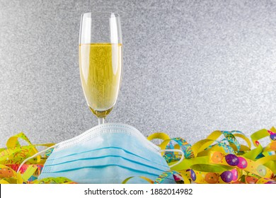 a glass of sparkling wine, a streamer as a background and a silver glitter background, face mask covering the bottom of the glas as sysbol vor impact ov Covid-19 on new year's eve 2021