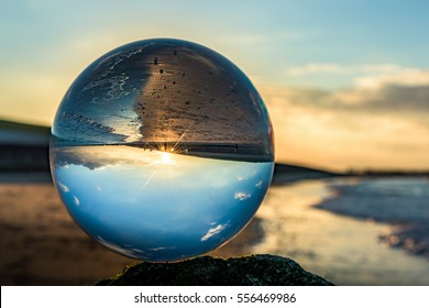 Glass sphere at the beach during sunset